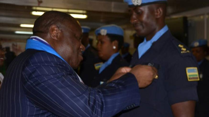 Joint Special Representative to UNAMID, Kingsley Mamabolo decorating one of the Rwandan Police peacekeepers.