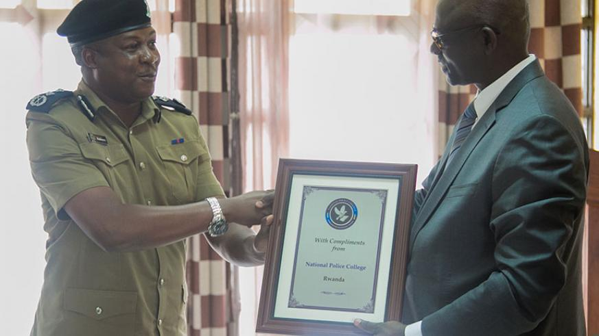 CP Kafeero Moses from Ugandan Police hands a gift to Minister Busingye on the behalf of his colleagues. (Photos by Faustin Niyigena)