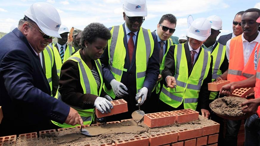 (L-R) Chairman of the Board of Hakan AS ,Ahmet Karasoy, State Minister Kamayirese, Minister Musoni  lay a foundation stone where the 80MW Peat-Fired Power Plant will be constructed. ( All photos by Sam Ngendahimana)