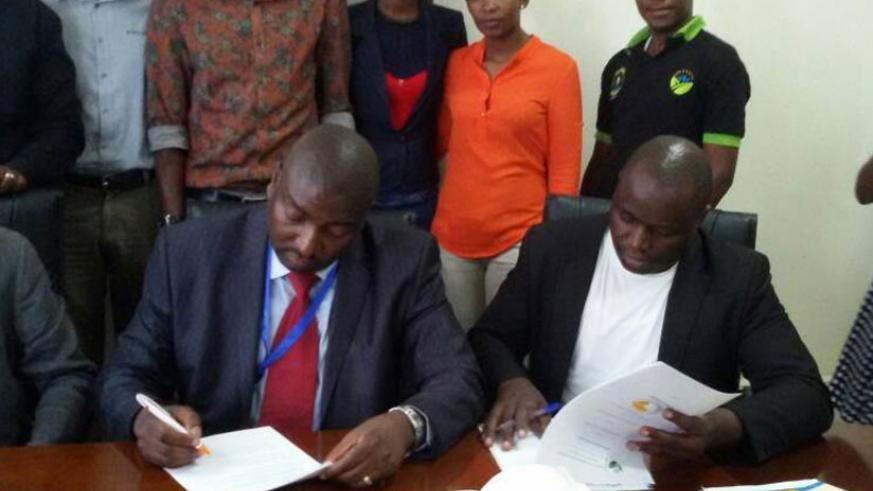 Hategekimana (L) and Ariho sign the agreement in Kigali yesterday. (Elias Hakizimana)