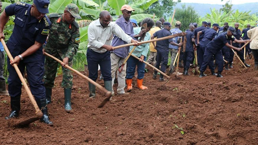Senior government and security officials, and residents take part in Umuganda to construct a road in Rugarama Village in Giti Sector. (File)