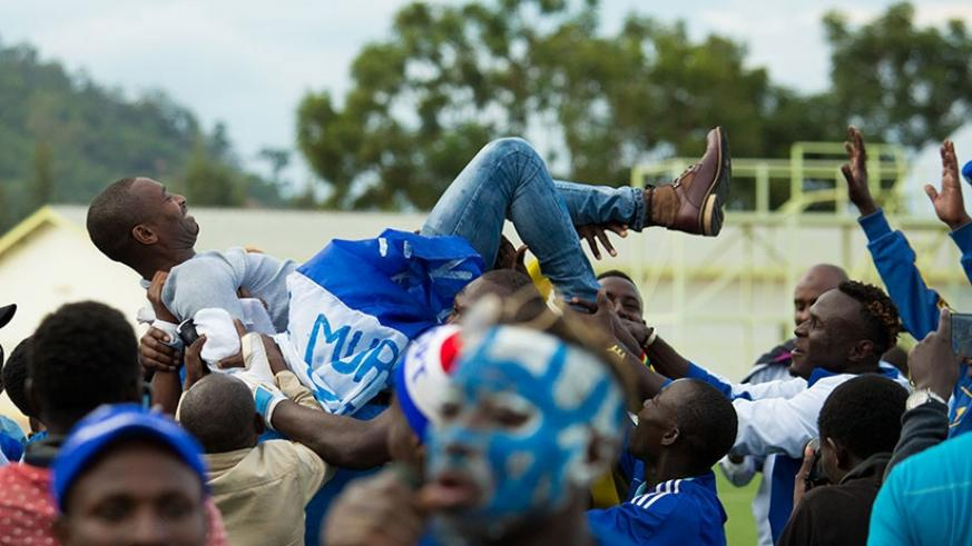 Rayon Sports coach Djuma  Masudi is carried shoulder-high by his players after winning the league on Wednesday at Stade de Kigali. (Timothy Kisambira)