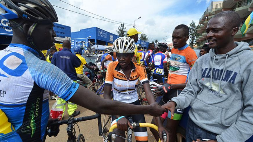 Felix Sempoma, right, shakes hands with a rider before the start of a past national race. / Sam Ngendahimana
