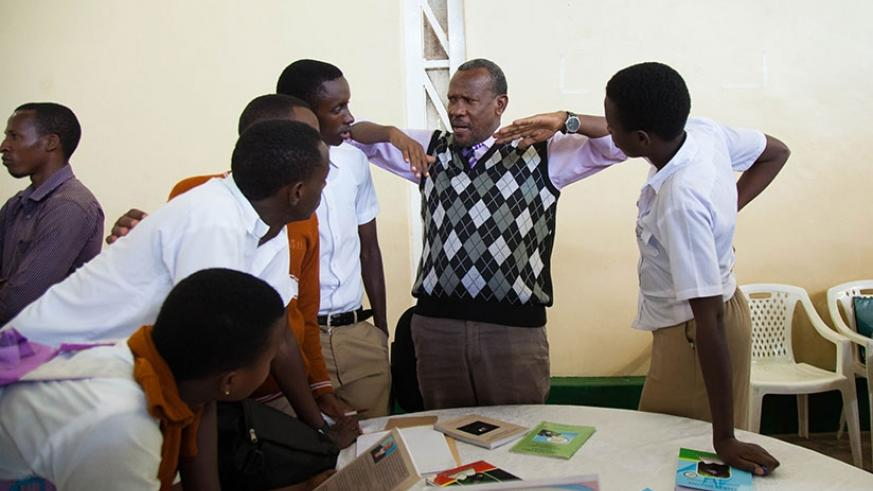 An exhibitor explains to a group of students. (Nadege Imbabazi)
