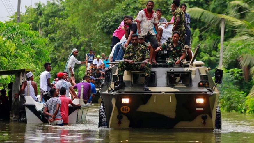 Sri Lankan soldiers evacuate flood victims while also carrying relief material, at a flooded area in Wehangalla village in Kalutara district, yesterday.  Net photo.