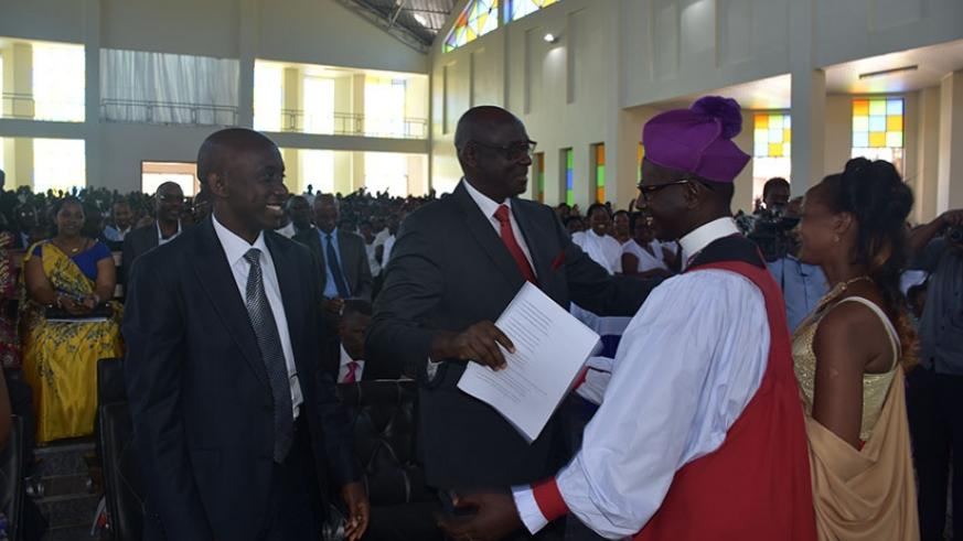 Justice minister Johnston Busingye (C) congratulates Bishop Gahima upon his consecration as Kaboneka (L) looks on yesterday. Jean d'Amour Mbonyinshuti.