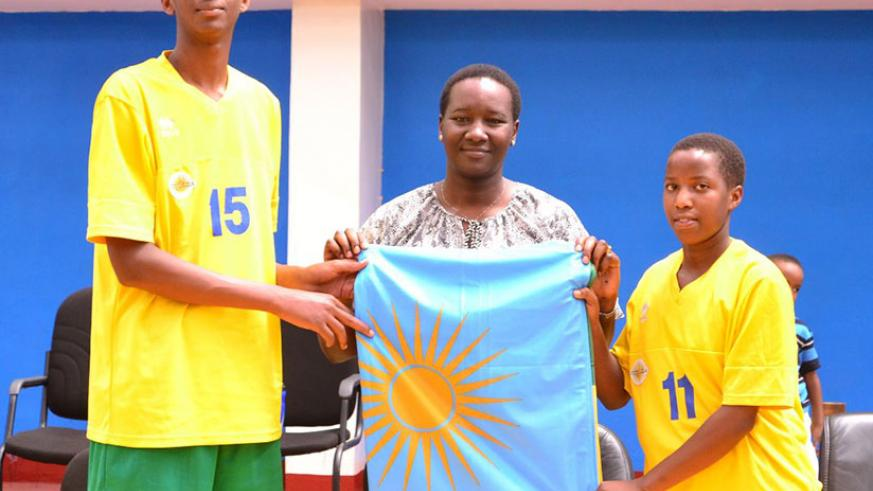 Minister Uwacu hands over the national flag to the captains of both teams at Amahoro Indoor Stadium on Sunday. / Courtesy