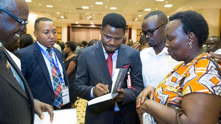 MP Bamporiki signs books ahead of the launch of 'My Son, It Is A Long Story' in Kigali on Sunday. (Courtesy photos)