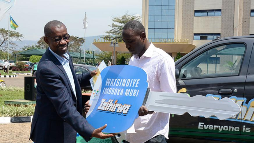 Pascal Ruganintwari, deputy commissioner general at RRA, hands over a dummy key for the car to Aaron Uwimana. / Appolonia Uwanziga