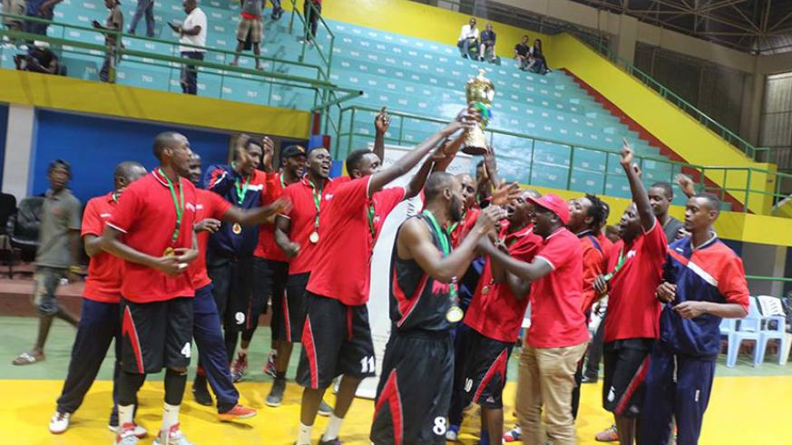 REG players and coaching staff lift their title in celebration after winning the GMT regional edition on Sunday at Amahoro indoor stadium. (G. Asiimwe)