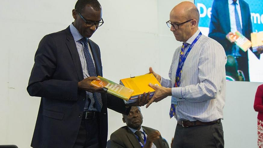 Education minister Papius Musafiri (L) receives books from the Vice- Chancellor of University of Rwanda, Prof. Phillip Cotton, during an international scientific conference that opened in Kigali yesterday. (Nadege Imbabazi)