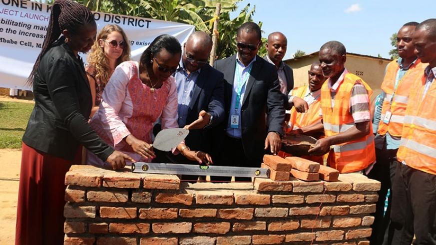 Kamuyumbu (L), Angelique Mukunde, the kicukiro vice-mayor in charge of finance (2nd left),  Sano (1st right) and other officials lay the foundation stone for the works in Masaka. John Mbaraga.