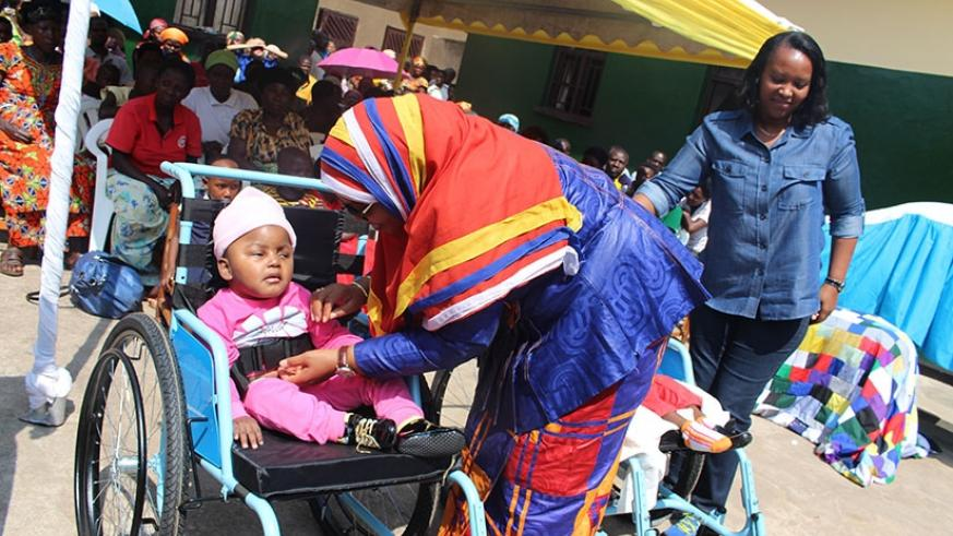 Senate vice-president Fatou Harerimana takes care of a disabled child during the tour of the orphanages with Minister Nyirasafari (R) yesterday. Frederic Byumvuhore.