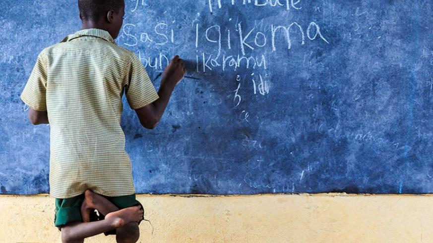 A physically handicapped learner writes on a blackboard during a lesson at a school in Bumbogo Sector, Gasabo District. Timothy Kisambira.
