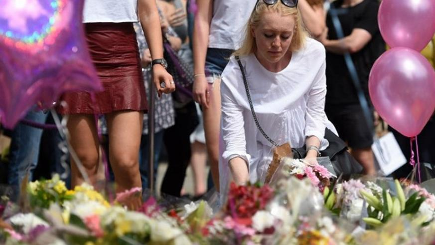 A woman places flowers in St Ann's Square in Manchester, northwest England. (Net photo)