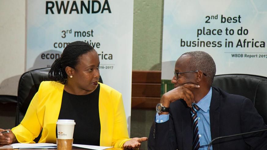 Clare Akamanzi, the CEO of RDB, chats with Stephen Ruzibiza, CEO of the Private Sector Federation, during press conference yesterday. / Nadege Imbabazi
