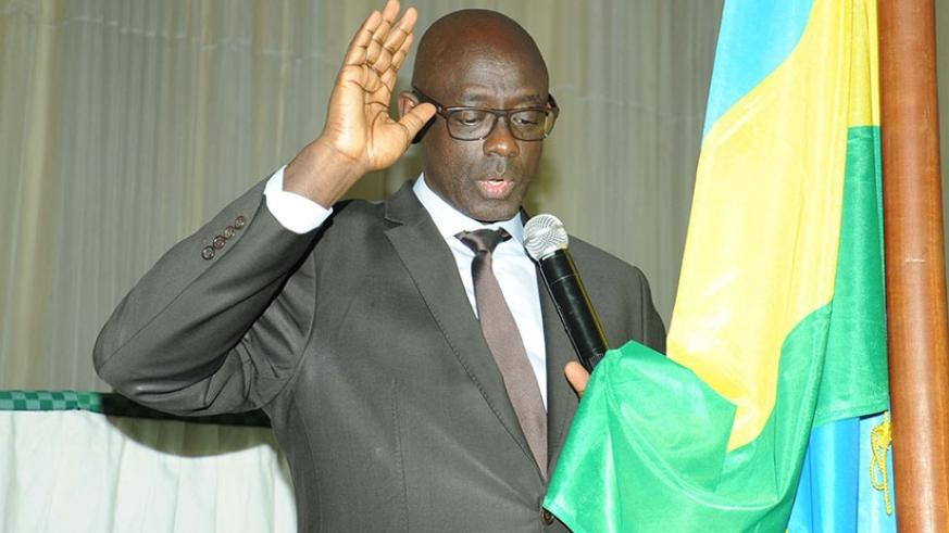 Minister Busingye takes oath before delivering his speech. (Francis Byaruhanga)