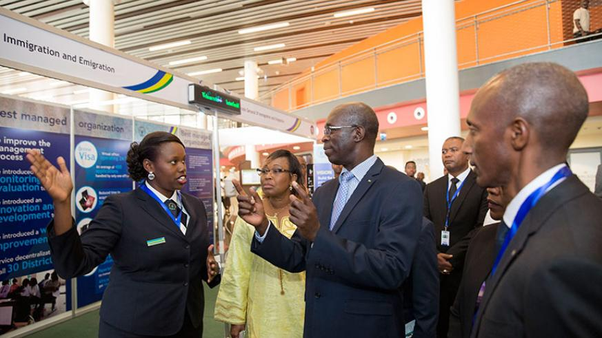 Prime Minister Anastase Murekezi (C) tours an exhibition stand of the Directorate of Immigration and Emigration on the sidelines of Africa Public Service Day conference at Kigali C....