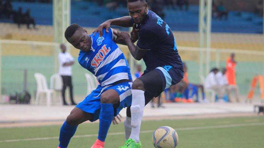 Rayon Sports midfielder Pierrot Kwizera (L) vies for the ball with a Police FC defender during the second leg match on Wednesday. / Sam Ngendahimana