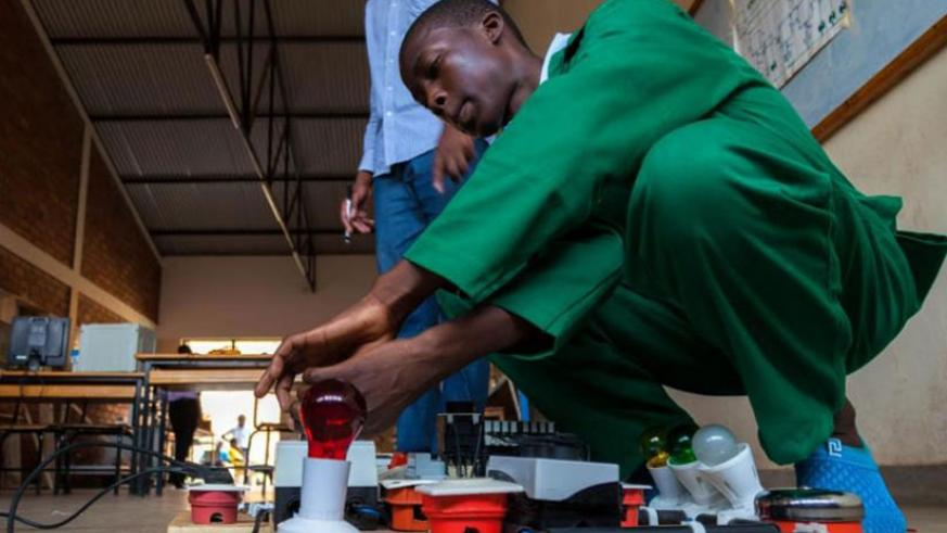 Rogers Dushimiyimana, a former TVET student of Alliance High School, performs an experiment. File.