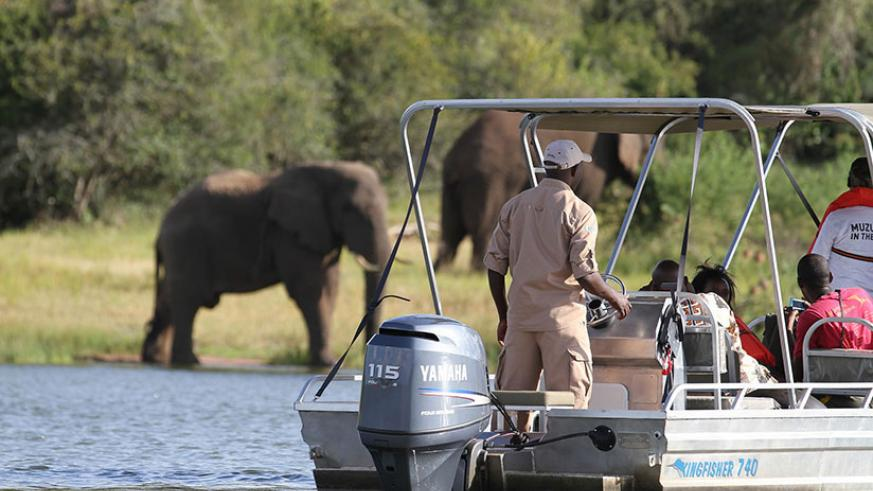 Tourists view elephants from a boat in Akagera National Park. / Courtesy