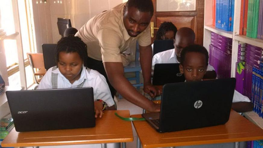 A teacher at Little Bears guides his pupils during their computer class.