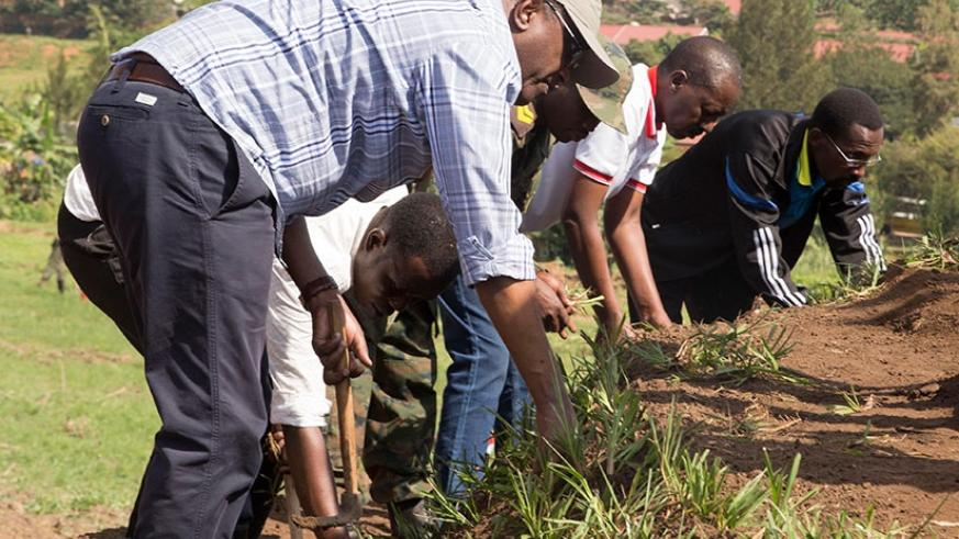 Dr Biruta and other officials plant grass during a special community exercise (Umuganda) last month at Nyandungu Wetland which is being developed into an Eco-Tourism Park. (Courtesy)