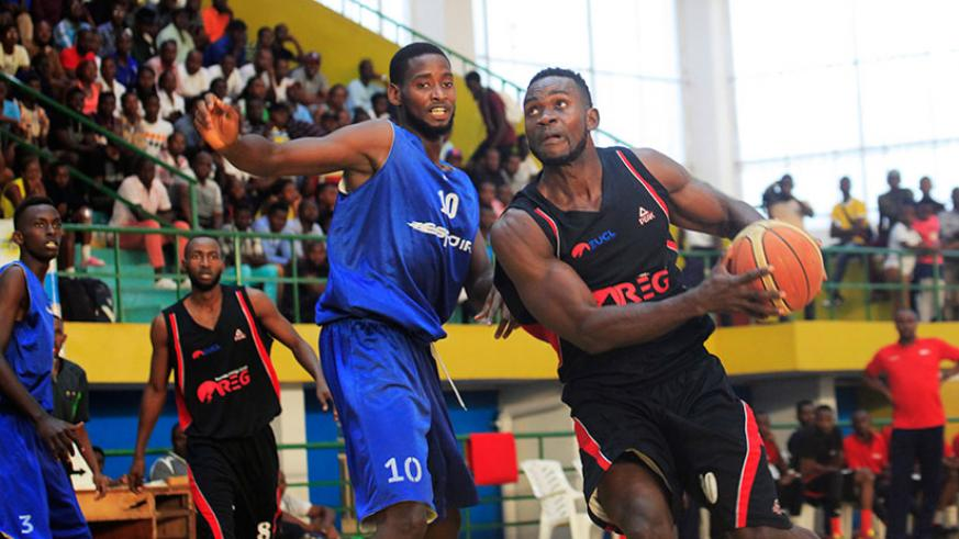 REG's Bienvenu Ngandu goes for points as Espoir captian Olivier Shyaka tries to block him during Genocide memorial tourney. / Sam Ngendahimana