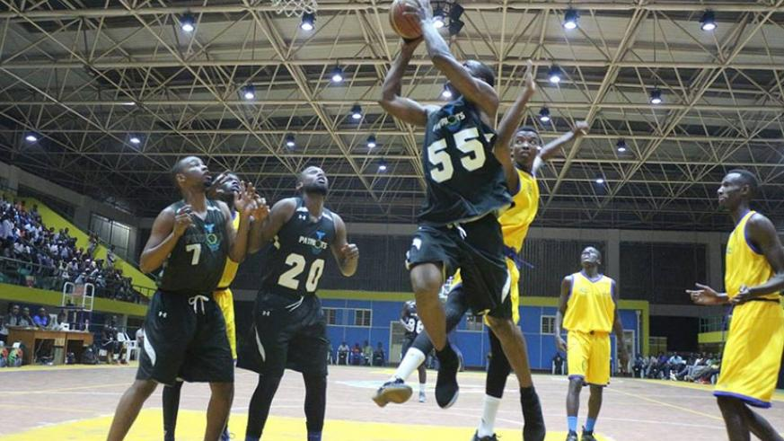 Patriot's center player Elie Kaje jumps in the air to drop two points as IPRC-Kigali players try to block him during game one on Friday. G. Asiimwe