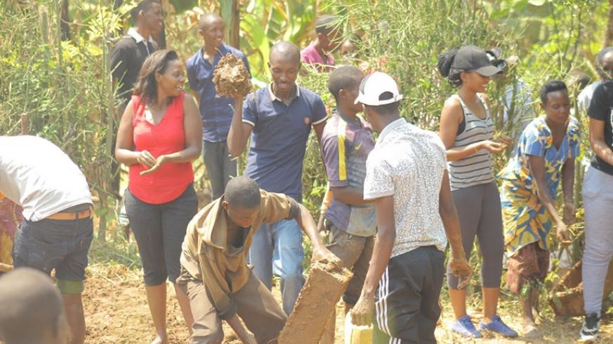 Members participate in the making of bricks for construction of Veneranda Mukandamage's house. (Donata Kiiza)