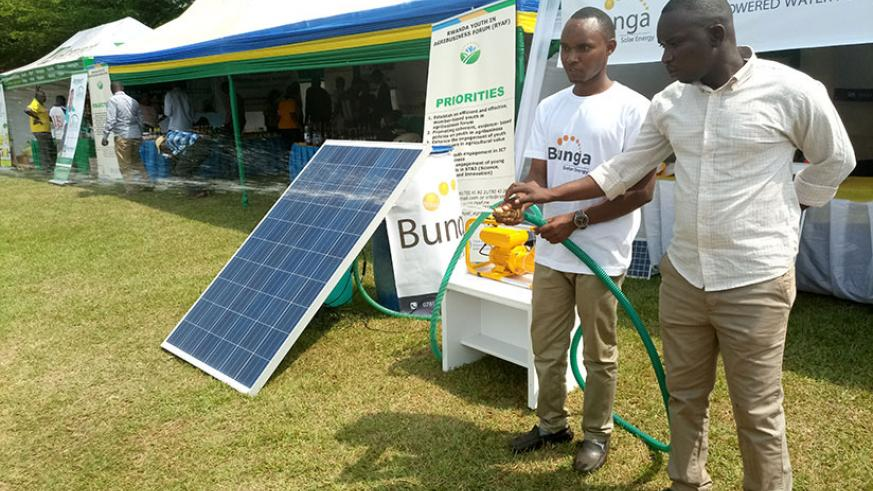 An exhibitor (L) and a farmer test a solar powered irrigation  Technology  at the agriculture  show, at Mulindi Show ground in Kigali on Friday. (Emmanuel  Ntirenganya)