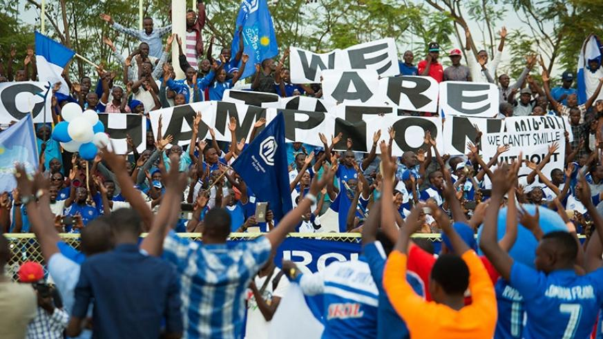 Rayon Sport players join fans with the banner of 'We are the champions' after defeating Mukura in May to win the 2016/17 league title. (T. Kisambira)