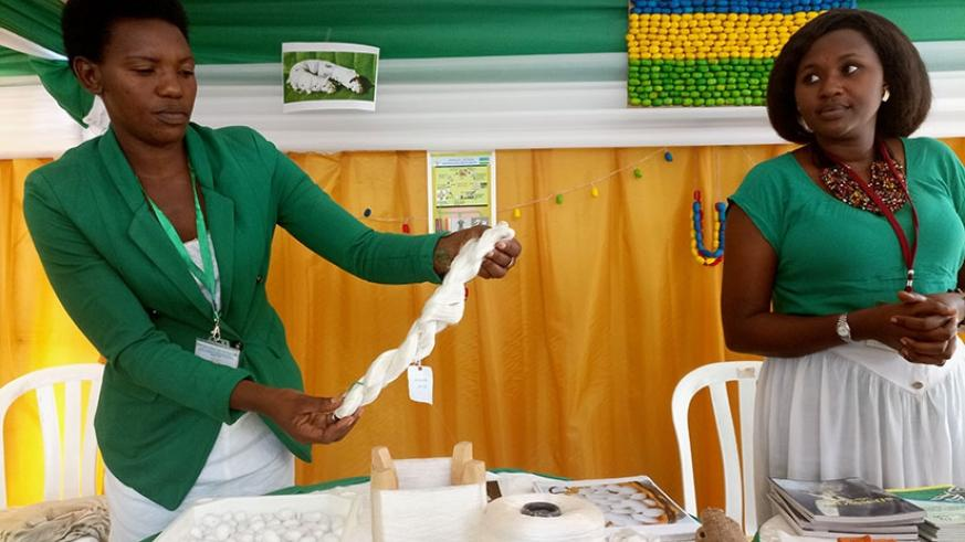 NAEB workers showcase a sample of silk yarn during an expo. Top right is a Rwandan flag design made from silk cocoons. (Photo/Emanuel Ntirenganya)