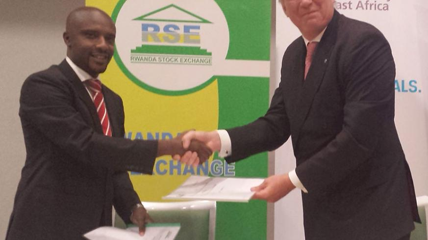 Rwabukumba (left) and Smith exchange the partnership deal documents on Wednesday. Under the agreement, the institute will build the capacity of financial market players. / Elisee Mpirwa
