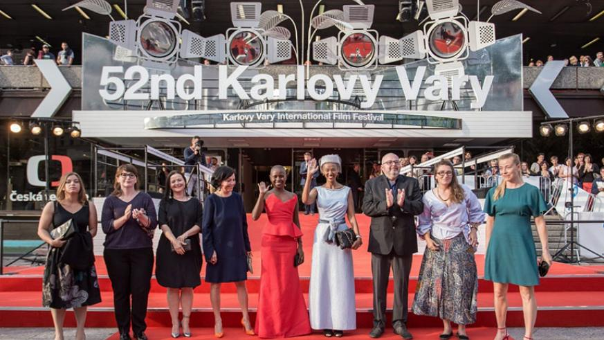 Rwandan actress Umuhire and Murenzi, the film's production designer and art director (in a sky blue gown), on the red carpet with other delegates at the Karlovy Vary International ....