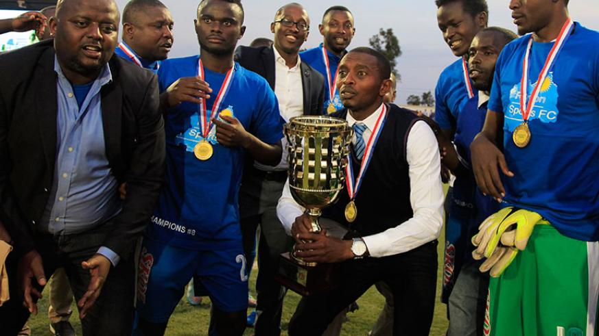 Masudi surrounded by his players prepares to raise the league trophy yesterday. / Photos: Sam Ngendahimana