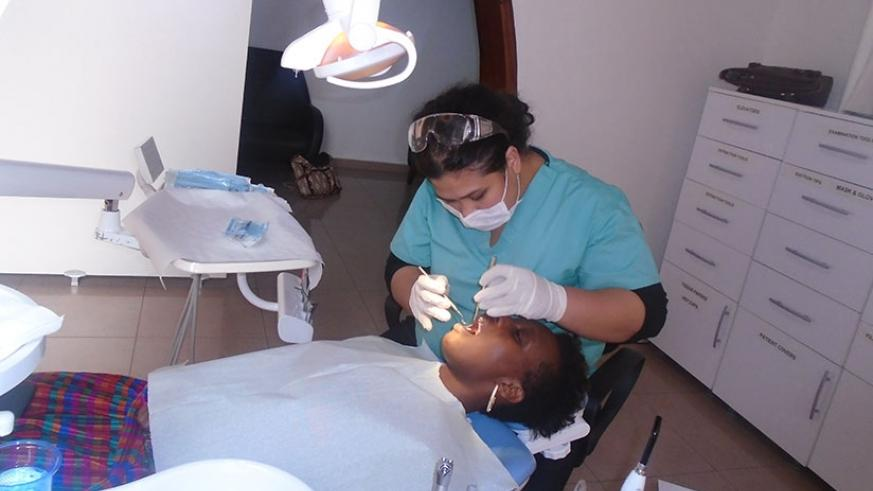 Dr Kristine Mae T Ferrer, a dentist at Deva Medical Consultancy in Nyarutarama, Kigali, attends to a patient with a dental problem./ Lydia Atieno.
