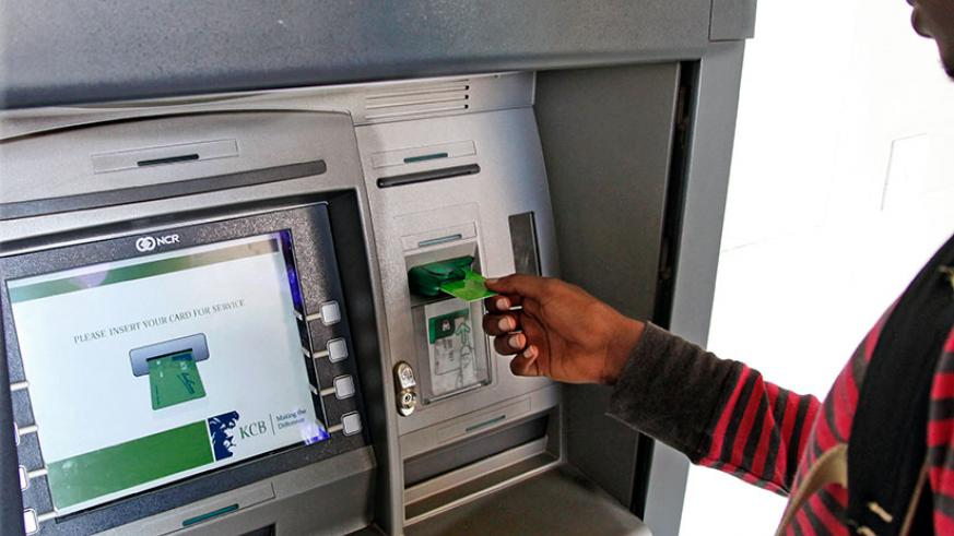 A client withdraws money from an ATM. Timothy Kisambira.