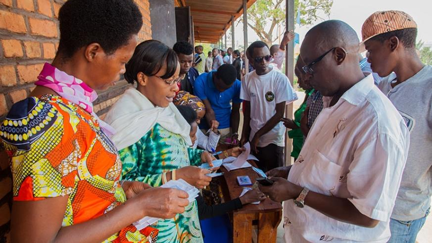 People collect their voter cards at Sainte Famille polling station during the 2015 referendum on the Constitution. Faustin Niyigena.