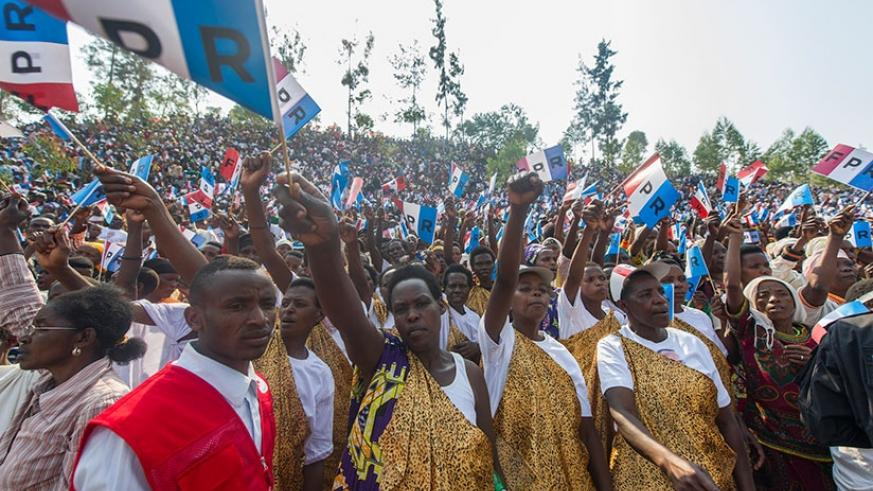 Residents of Nyaruguru raise RPF flags as they listen to RPF presidential flag bearer Paul Kagame yesterday. Thousands turned up to show their support on day 2 of the presidential ....