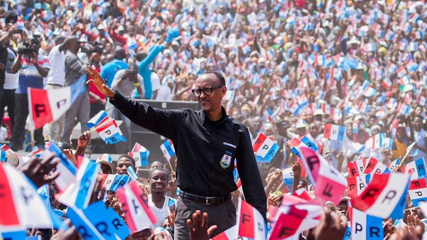 Incumbent President Kagame greets residents of Nyaruguru after arriving in the Southern province during Day 2 of the presidential campaigns yesterday. The RPF presidential flag bea....