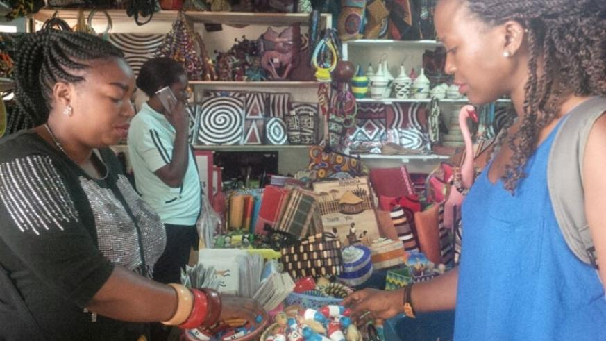 Uwamahoro (left) attends to a customer. The crafts dealer has added RPF paraphernalia to boost her earnings. / Joan Mbabazi