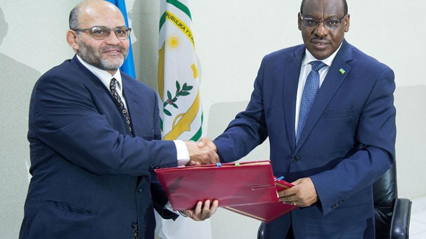 WB's Gammal (L) exchanges documents with minister Gatete after the signing ceremony in Kigali. / Timothy Kisambira.