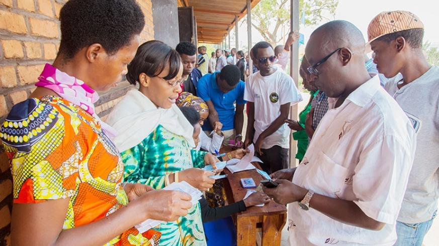 Citizens search for their voter cards at Ecole Sainte Famille polling station in Kigali  File
