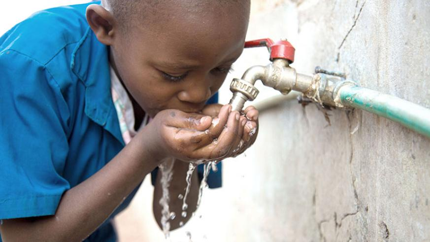 A school child in Muhanga District drinks water. More than 85% of Rwandans have access to clean water. (Timothy Kisambira)