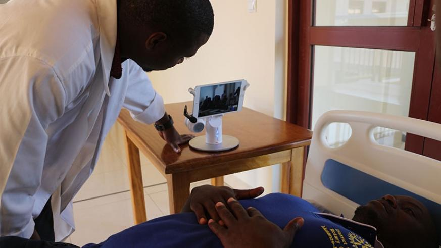 A doctor attending to a patient at a local health facility seeks another doctor's opinion by use of  telemedicine technology. Michel Nkurunziza.