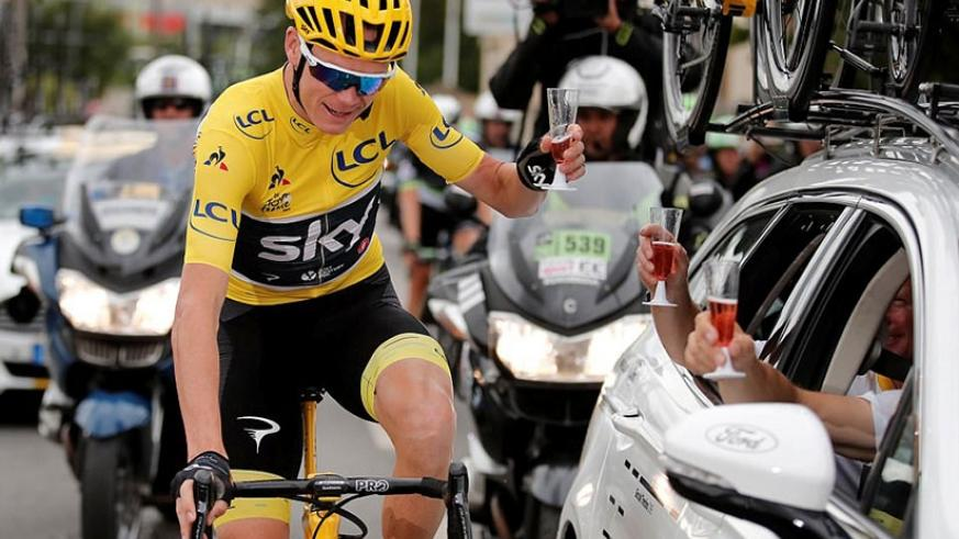 The 32-year-old winner takes a glass of champagne from his team during the processional final stage of the famous race. (Net photo)
