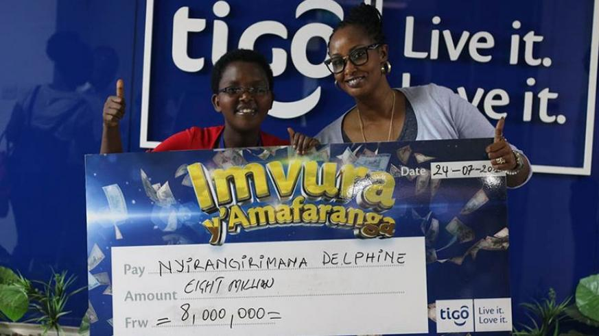 Irangaza (left) after receiving the dummy cheque from Tigo deputy CEO, Chantal Umutoni Kagame. / Courtesy.