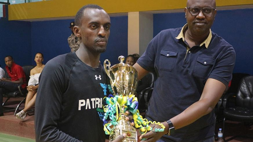 Aristide Mugabe receives the playoffs trophy from Ferwaba president Desire Mugwiza on Saturday after defeating REG. Courtesy