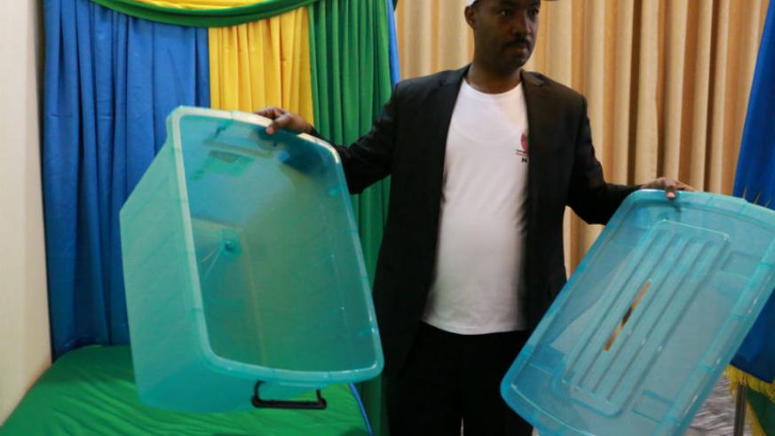 Kayonga displaying to the voters an empty ballot box before the elections began in China. / Courtesy